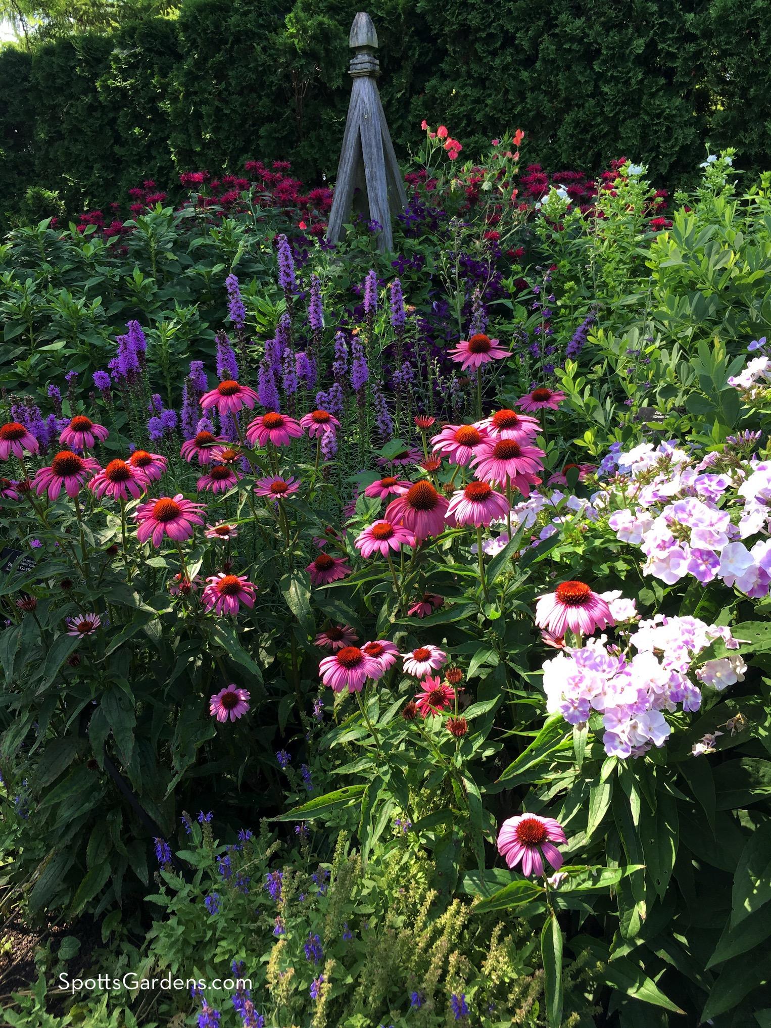 Wooden garden tuteur with blooming flowers
